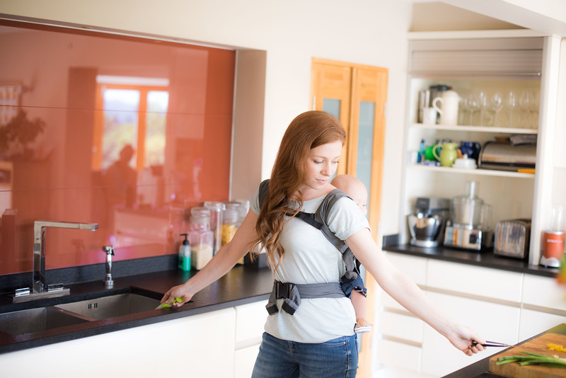Izmi_Baby_Carrier_Mid_Grey_Lifestyle_Back_Carry_In_Kitchen_Between_Work_Surfaces.jpg