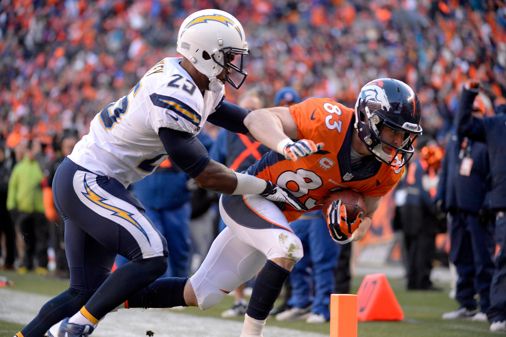 . DENVER, CO - JANUARY 12: Denver Broncos wide receiver Wes Welker (83) takes the ball into the end zone for a second quarter touchdown pass San Diego Chargers defensive back Darrell Stuckey (25)The Denver Broncos vs. The San Diego Chargers in an AFC Divisional Playoff game at Sports Authority Field at Mile High in Denver on January 12, 2014. (Photo by John Leyba/The Denver Post)