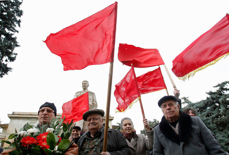 . People carry flowers and red flags in front of a statue of the late Soviet leader Josef Stalin during a ceremony to mark the 60th anniversary of Stalin\'s death in his hometown of Gori, about 50 miles west of Georgia\'s capital on March 5, 2013. REUTERS/David Mdzinarishvili