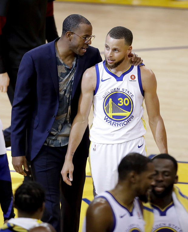 . Golden State Warriors guard Stephen Curry (30) walks with injured forward Andre Iguodala, in suit, after scoring against the Cleveland Cavaliers during the first half of Game 1 of basketball\'s NBA Finals in Oakland, Calif., Thursday, May 31, 2018. (AP Photo/Marcio Jose Sanchez)