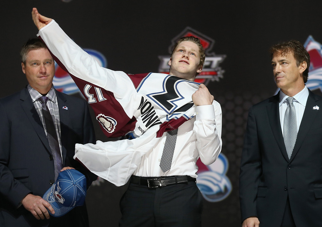 . Nathan MacKinnon (c) puts on his Colorado Avalanche jersey as he stands with head coach Patrick Roy (l) and Joe Sakic (r) after MacKinnon was selected number one overall in the first round by Colorado during the 2013 NHL Draft at the Prudential Center on June 30, 2013 in Newark, New Jersey.  (Photo by Bruce Bennett/Getty Images)