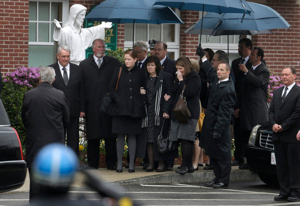 Description of . Mourners enter St. Patrick's Church in Stoneham, Mass., before a funeral Mass for Massachusetts Institute of Technology police officer Sean Collier, Tuesday, April 23, 2013. Collier was fatally shot on the MIT campus Thursday, April 18, 2013. Authorities allege that the Boston Marathon bombing suspects were responsible. (AP Photo/Steven Senne)