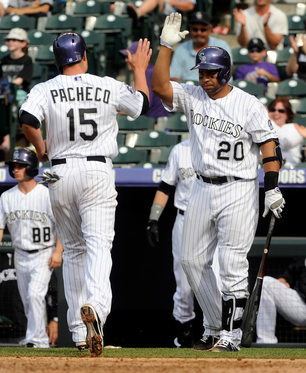 . Wilin Rosario, right, congratulated Jordan Pacheco after he scored in the ninth inning. The Colorado Rockies were defeated by the Miami Marlins 5-3 at Coors Field Thursday afternoon, July 25, 2013. Photo By Karl Gehring/The Denver Post