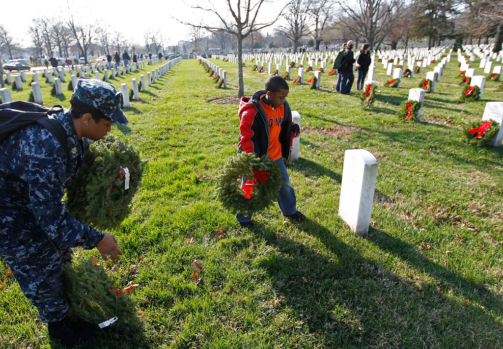 . Spencer Williams, 7, helps his mother, Navy HMC Shawntell Williams, to place holiday wreaths at the graves of fallen soldiers during Wreaths Across America Day at Arlington National Cemetery Saturday Dec. 10, 2011, in Arlington, Va.  (AP Photo/Jose Luis Magana)