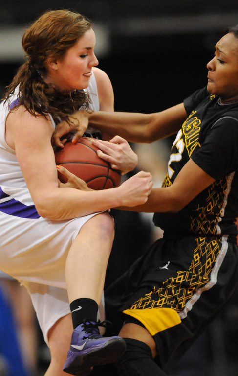 . Red Wing Wingers guard Tesha Buck (12), left, and DeLaSalle Islanders forward Tyseanna Johnson (22) wrestle for the ball in the second half. (Pioneer Press: John Autey)