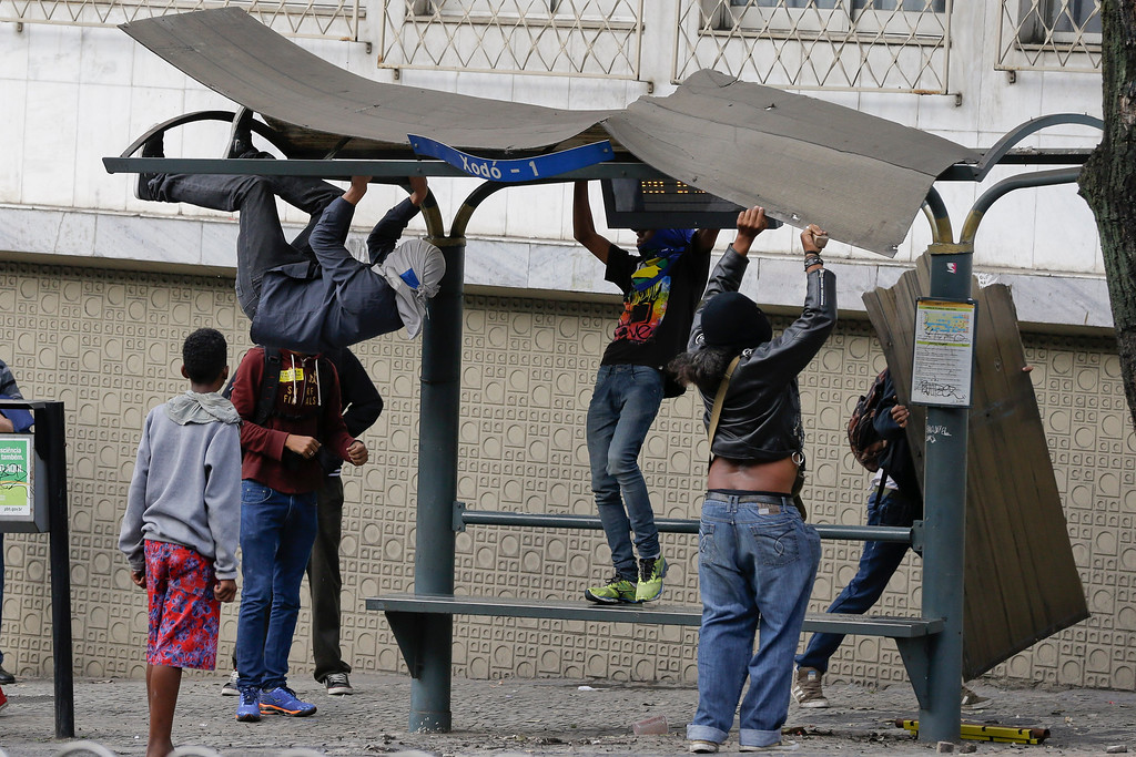 . Demonstrators destroy a bus stop during a protest against the 2014 World Cup in Belo Horizonte, Brazil, Thursday, June, 12, 2014.  (AP Photo/Fernando Vergara)