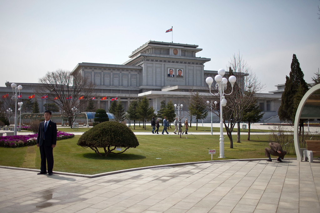 . A man, left, in his suit, stands posing for photos while a soldier, right, squats down examining the lawn outside the Kumsusan Memorial Palace in Pyongyang, North Korea, Monday, April 15, 2013. The palace, which was the official residence of Kim Il Sung until his death in 1994, is now a mausoleum where the two late leaders\' embalmed bodies lie in state. (AP Photo/Alexander F. Yuan)