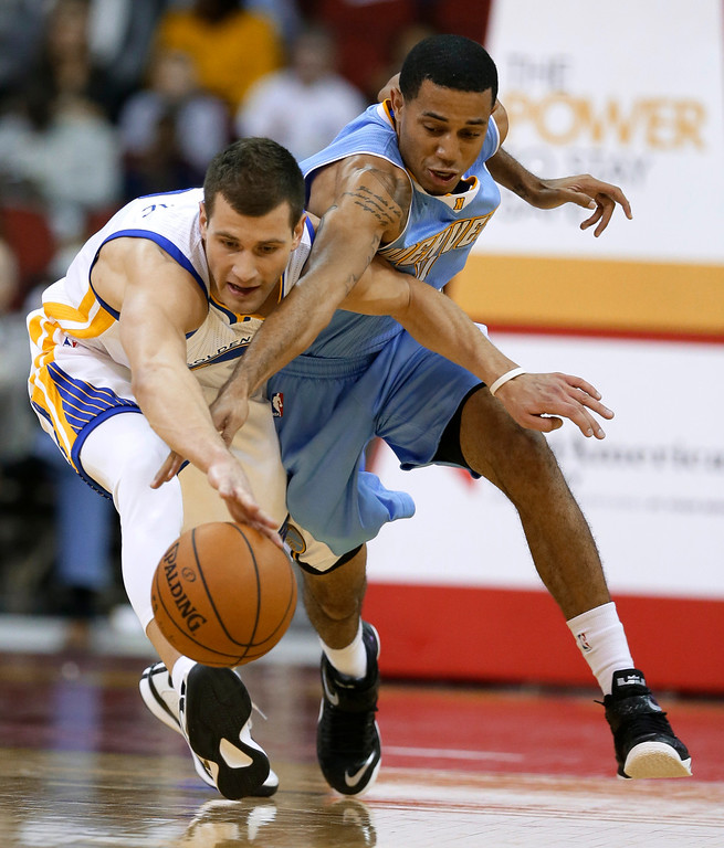 . Golden State Warriors guard Nemanja Nedovic, left, reaches for a loose ball with Denver Nuggets guard Erick Green during the second half of a preseason NBA basketball game, Thursday, Oct. 16, 2014, in Des Moines, Iowa. Golden State won 104-101. (AP Photo/Charlie Neibergall)