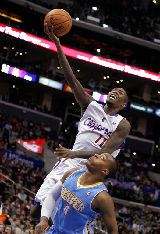 . Los Angeles Clippers guard Jamal Crawford (11) shoots over Denver Nuggets guard Randy Foye (4) during the first half of an NBA basketball game in Los Angeles on Saturday, Dec. 21, 2013. (AP Photo/Alex Gallardo)