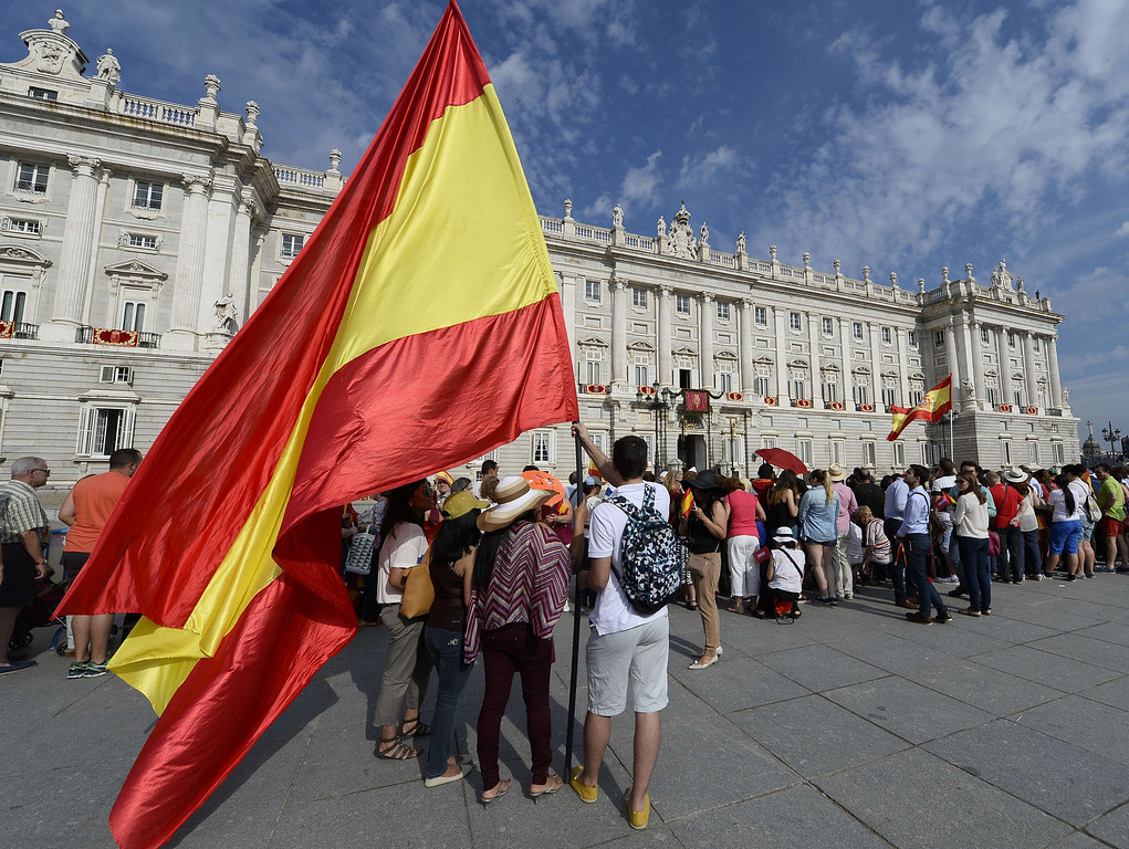 . A man waves a Spanish flag outside the Royal Palace in Madrid on June 19, 2014 before a swearing in ceremony of Spain\'s new King before both houses of parliament. Spain\'s King Felipe VI begins a new reign today already facing a threat to the unity of his kingdom as the northeastern region of Catalonia fights to hold an independence referendum on November 9. AFP PHOTO / GERARD  JULIEN/AFP/Getty Images
