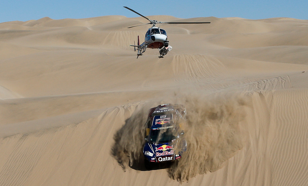 . A helicopter flies over driver Nasser Al-Attiyah of Qatar and co-driver Lucas Cruz of Spain competing in the 4nd stage of the 2013 Dakar Rally from Nazca to Arequipa, Peru,  Tuesday, Jan. 8, 2013. The race finishes in Santiago, Chile, on Jan. 20. (AP Photo/Victor R. Caivano)