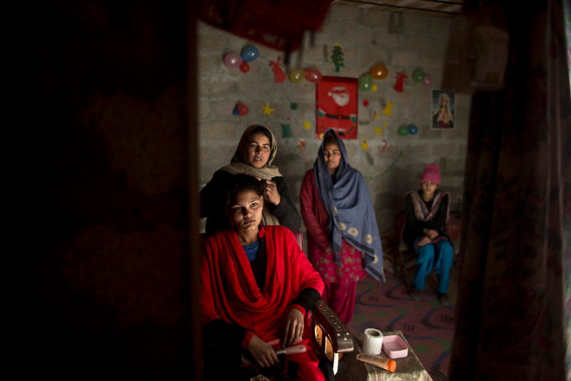 . Pakistani Christian Maria Akbar, 15, is reflected in a mirror, while having her make up done by hairdresser Razia Rehmat, 39, in preparation for Christmas holiday, at a hair salon in a slum that hosts Christian families, on the outskirts of Islamabad, Pakistan, Wednesday, Dec. 24, 2014. (AP Photo/Muhammed Muheisen)