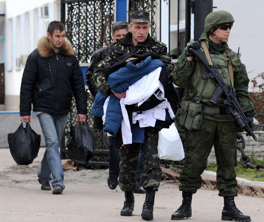 . Ukrainian officers leave as Russian soldiers stand guard at the Ukrainian navy headquarters in the Crimean city of Sevastopol on March 19, 2014.  Ukrainian servicemen filed out of navy headquarters in Sevastopol on Wednesday with tears in their eyes after the base was seized by pro-Moscow militants, Russian troops and Cossack forces.  The assault began when some 200 unarmed militants -- some of them in balaclavas -- sawed through a fence and overran the base while the Ukrainian servicemen barricaded themselves inside.  AFP PHOTO/  VIKTOR  DRACHEV/AFP/Getty Images