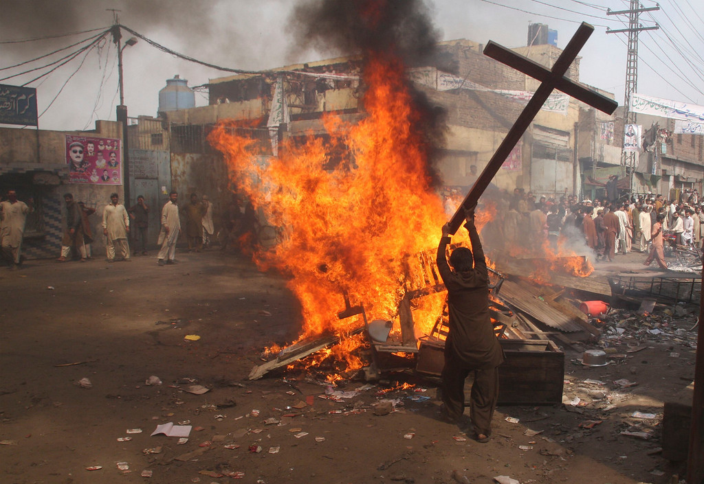 . A demonstrator burns a cross during a protest in the Badami Bagh area of Lahore March 9, 2013. An enraged mob torched dozens of houses located in a Christian-dominated neighbourhood of Lahore on Saturday, local media reported. REUTERS/Adrees Hassain