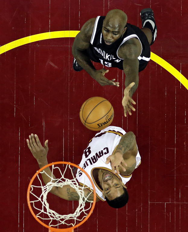 . Brooklyn Nets\' Quincy Acy, top, drives to the basket against Cleveland Cavaliers\' Channing Frye during the first half of an NBA basketball game, Friday, Jan. 27, 2017, in Cleveland. (AP Photo/Tony Dejak)