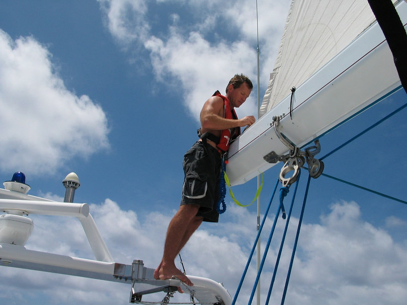 Sailing from Bora Bora to Hawaii -- Callum inspects the clew of the mainsail