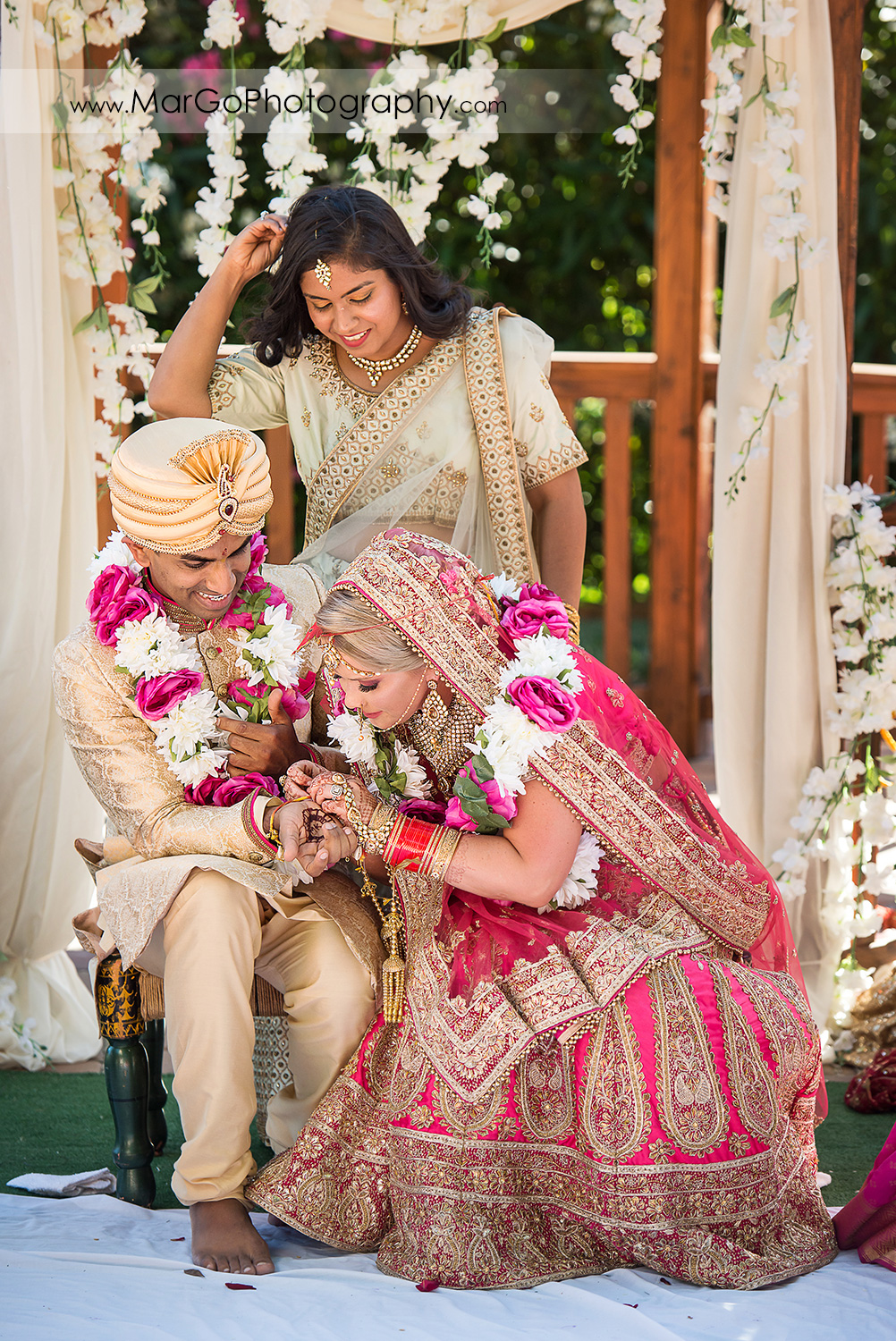 Indian bride untying Kautuka red-yellow coloured ritual protection thread from groom's hand during wedding ceremony at Elliston Vineyards in Sunol