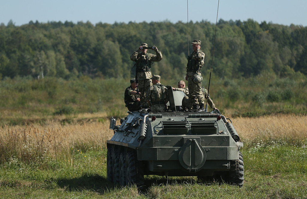 ". Ukrainian soldiers stand on an aromoured personnel carrier during reconnaissance training on the second day of the ""Rapid Trident\"" NATO military exercises on September 16, 2014 near Yavorov, Ukraine. (Photo by Sean Gallup/Getty Images)"