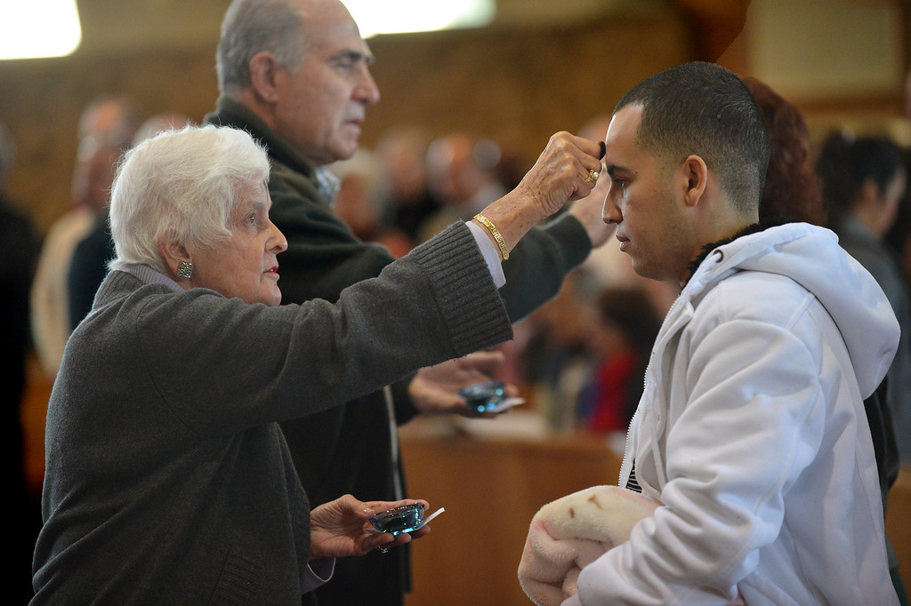 . Barbara Karabinos of Antioch, left, puts ashes on the forehead of Ronald Baez, of Antioch, during Ash Wednesday mass  at Holy Rosary Church in Antioch, Calif., on Wednesday Sept. 13, 2013. (Dan Rosenstrauch/Staff)