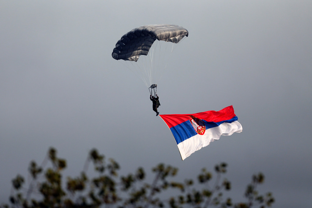 . A Serbian army paratrooper descends during a military parade in Belgrade, Serbia, Thursday, Oct. 16, 2014.  (AP Photo/Marko Drobnjakovic)