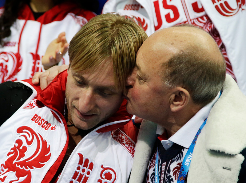 . Evgeny Plyushchenko of Russia, left, is embraced by his coach Alexei Mishin as he waits for his results in the men\'s team short program figure skating competition at the Iceberg Skating Palace during the 2014 Winter Olympics, Thursday, Feb. 6, 2014, in Sochi, Russia. (AP Photo/Darron Cummings, Pool)