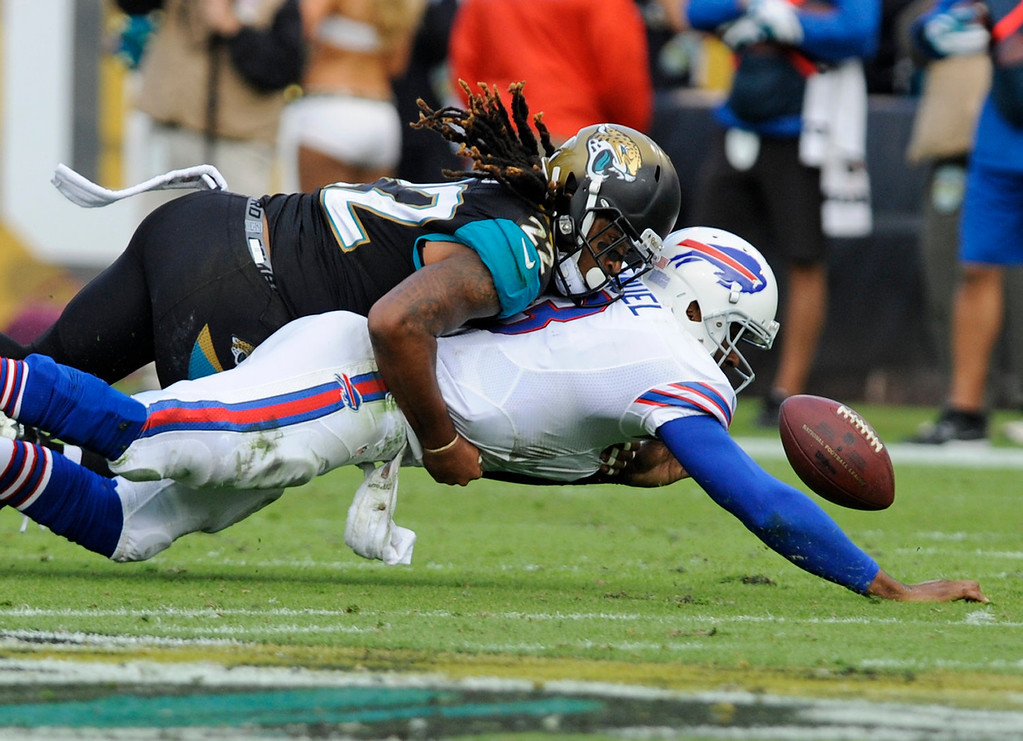 . Buffalo Bills quarterback EJ Manuel, right, fumbles the ball as he is hit by Jacksonville Jaguars free safety Winston Guy, left, during the second half of an NFL football game in Jacksonville, Fla., Sunday, Dec. 15, 2013. (AP Photo/Stephen Morton)