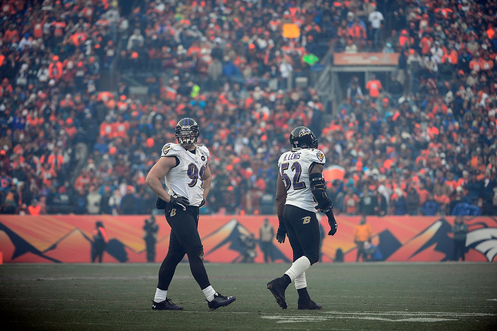 Description of . Baltimore Ravens outside linebacker Paul Kruger (99) and Baltimore Ravens inside linebacker Ray Lewis (52) walk off the field in the second quarter. The Denver Broncos vs Baltimore Ravens AFC Divisional playoff game at Sports Authority Field Saturday January 12, 2013. (Photo by AAron  Ontiveroz,/The Denver Post)
