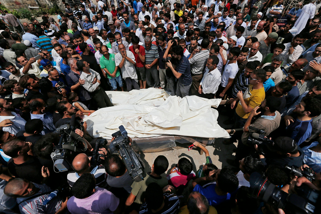 . Mourners gather around the bodies of seven members of the Kelani family, killed overnight by an Israeli strike in Gaza City, during their funeral in Beit Lahiya, northern Gaza Strip, on Tuesday, July 22, 2014. Ibrahim Kelani, 53, his wife Taghreed and their five children, were killed in the strike on a Gaza City high-rise. Ibrahim\'s brother Saleh Kelani said Tuesday that his brother and his brotherís children, ranging in age from four to 12, had German citizenship, while his wife had not. The family had rented the apartment in the high-rise after fleeing their home in the northern Gaza town of Beit Lahiya which came under heavy shelling by the Israeli army. (AP Photo/Lefteris Pitarakis)