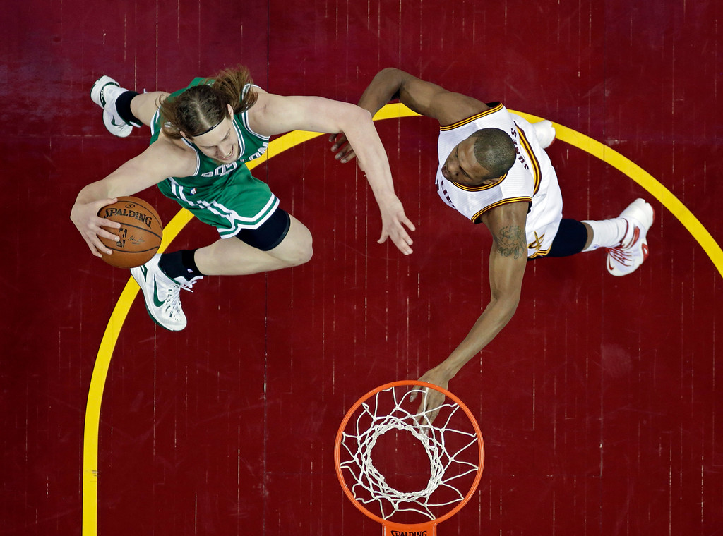 . Boston Celtics\' Kelly Olynyk, left, shoots against Cleveland Cavaliers\' James Jones in a first round NBA playoff basketball game Sunday, April 19, 2015, in Cleveland. (AP Photo/Tony Dejak)