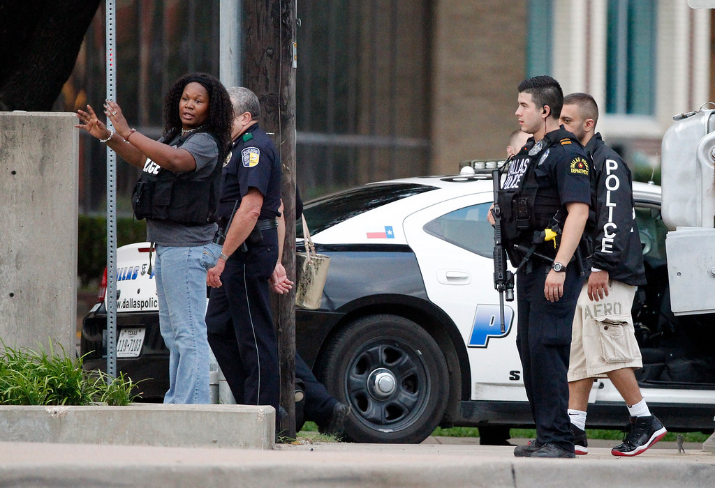 . Dallas police officers walk down Belleview Street one block away from police headquarters searching the area Saturday June 13, 2015, in Dallas.  A police sniper shot a cornered suspect in an overnight attack on the Dallas Police Department\'s headquarters, and authorities were checking Saturday to see if he was alive or dead. (AP Photo/Tony Gutierrez)