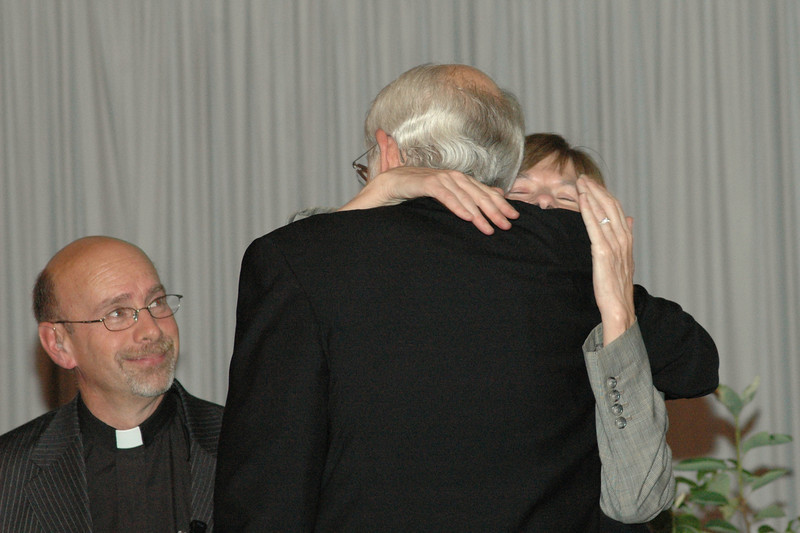 Presiding Bishop Mark S. Hanson gives Mary Beth Nowak, the assembly's meeting planner, a hug of appreciation as the Rev. Robert Schafer looks on.