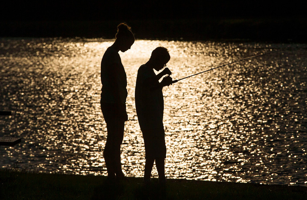 . A child fishes with his counselor at Camp Abilities in Brockport, New York, June 25, 2013. Camp Abilities is a not-for-profit week-long developmental camp using sports to foster greater independence and confidence in children who are blind, visually impaired, and deaf-blind. Photo taken June 25, 2013.     REUTERS/Mark Blinch