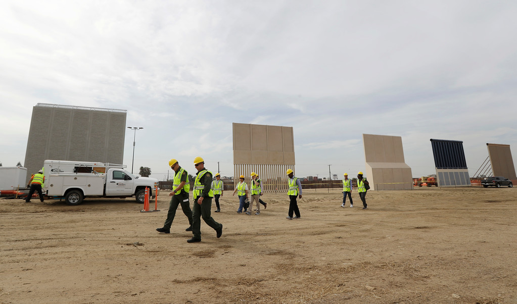 . People pass border wall prototypes as they stand near the border with Tijuana, Mexico, Thursday, Oct. 19, 2017, in San Diego. Companies are nearing an Oct. 26 deadline to finish building eight prototypes of President Donald Trump\'s proposed border wall with Mexico. (AP Photo/Gregory Bull)