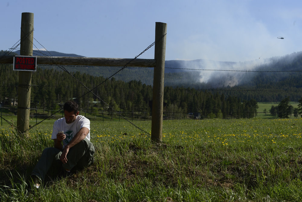 . John Orlando, 28, uses his phone to communicate with his parents -- who are 17-year residents of the area adjacent to the burn area -- as a fire burns in the hills west of Evergreen, Colorado. A fire started early in the afternoon on June 3, 2013 and by 3:30 p.m., residents of the surrounding area were told to evacuate. Many packed horses and other animals in trailers and drove them to nearby meadows. (Photo by AAron Ontiveroz/The Denver Post)