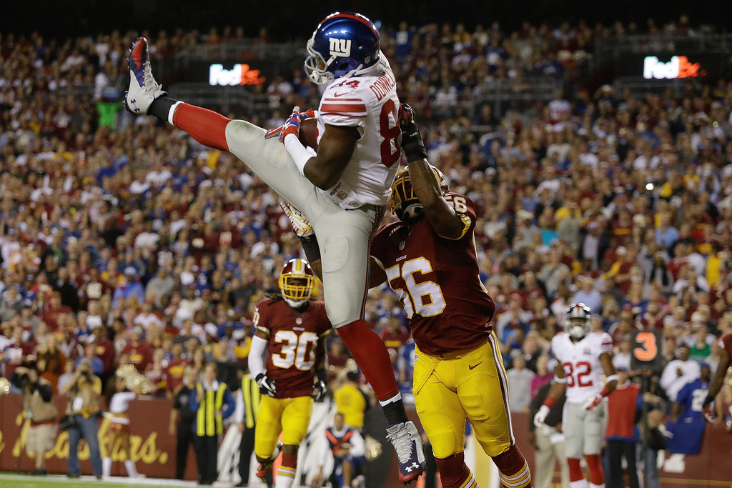 . New York Giants tight end Larry Donnell (84) pulls in a touchdown pass under pressure from Washington Redskins inside linebacker Perry Riley (56) during the first half of an NFL Thursday night football game in Landover, Md., Thursday, Sept. 25, 2014. (AP Photo/Patrick Semansky)