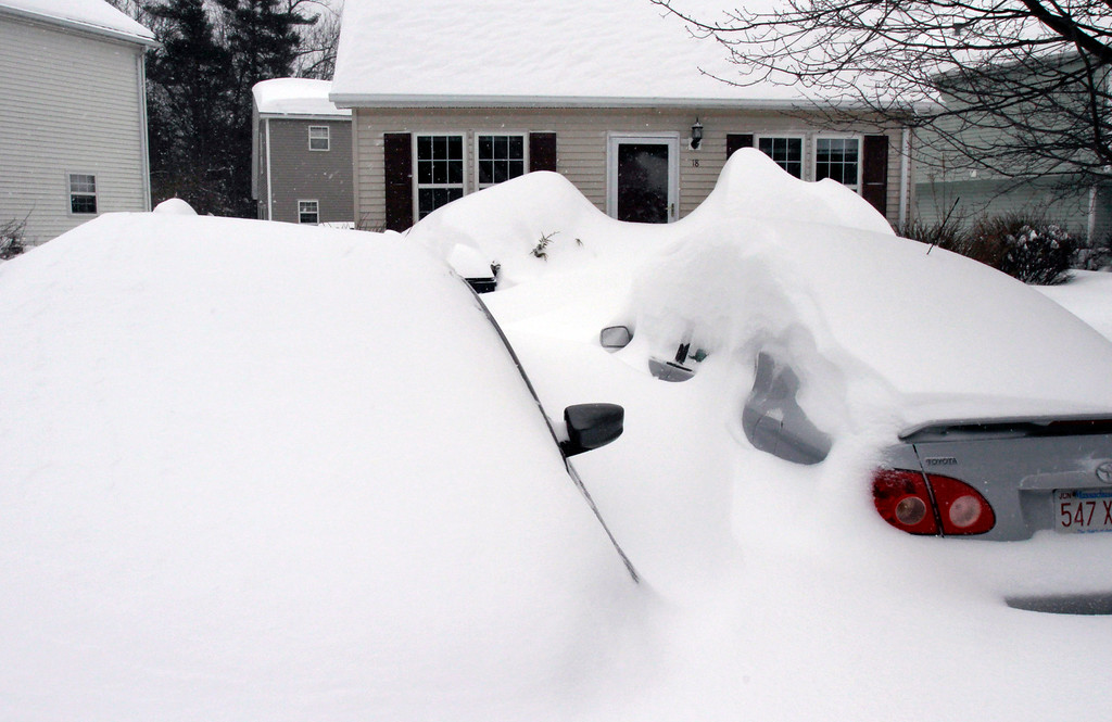 . Cars are buried by drifted snow from a winter snowstorm, Tuesday, Jan. 27, 2015, in Marlborough, Mass. A storm packing blizzard conditions spun up the East Coast early Tuesday, pounding parts of coastal New Jersey northward through Maine with high winds and heavy snow. (AP Photo/Bill Sikes)