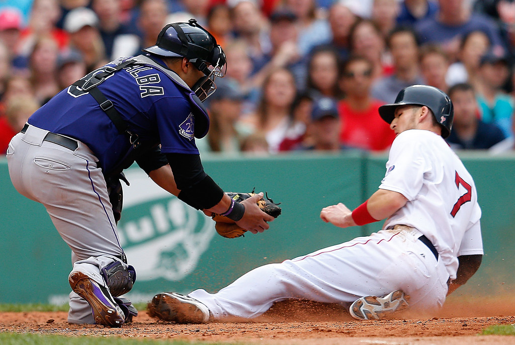 . Yorvit Torrealba #8 of the Colorado Rockies tags out Stephen Drew #7 of the Boston Red Sox at the plate in the 6th inning at Fenway Park on June 26, 2013 in Boston, Massachusetts.  (Photo by Jim Rogash/Getty Images)