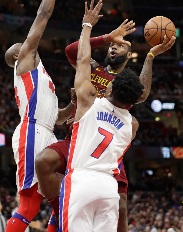. Cleveland Cavaliers\' LeBron James, back, shoot over Detroit Pistons\' Anthony Tolliver, left, and Stanley Johnson in the first half of an NBA basketball game, Sunday, Jan. 28, 2018, in Cleveland. The Cavaliers won 121-104. (AP Photo/Tony Dejak)