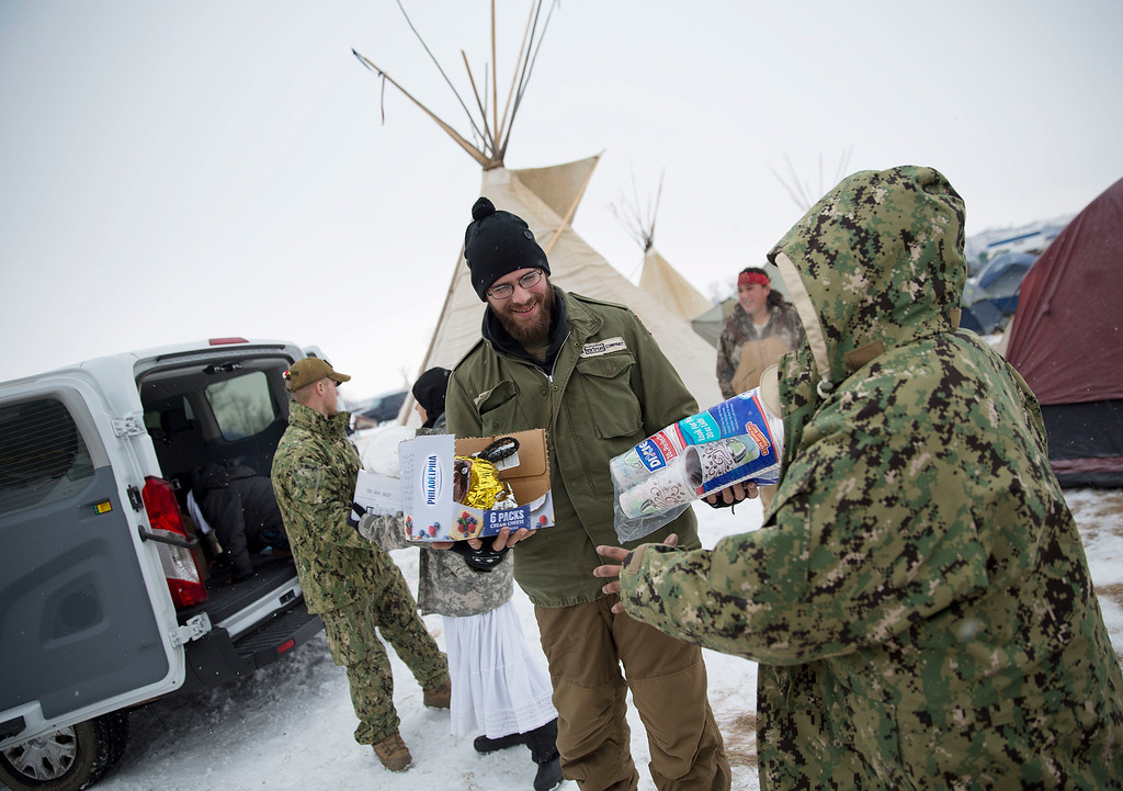 . U.S. Marine veteran Joe Slackie, of Oceanside, Calif., center, helps unload supplies at the Oceti Sakowin camp where people have gathered to protest the Dakota Access oil pipeline in Cannon Ball, N.D., Monday, Dec. 5, 2016. Many Dakota Access oil pipeline opponents who\'ve gathered for months in the camp in southern North Dakota are committed to staying despite wintry weather and demands that they leave. (AP Photo/David Goldman)