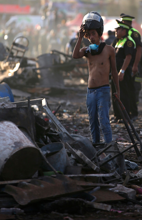 . A boy takes his helmet off as he pauses while working at the scorched ground of the open-air San Pablito fireworks market, in Tultepec, outskirts of Mexico City, Mexico, Tuesday, Dec. 20, 2016.  An explosion ripped through Mexico�s best-known fireworks market on the northern outskirts of the capital Tuesday, injuring scores and killing dozens, according to Mexican Federal Police. (AP Photo/Eduardo Verdugo)