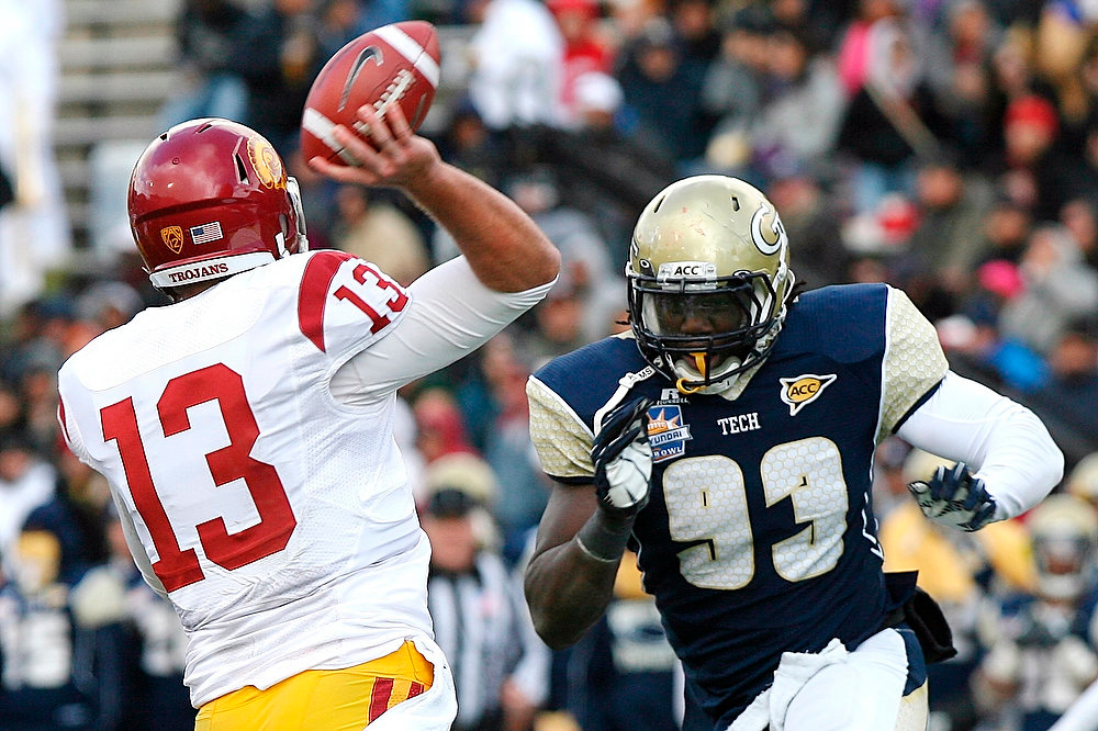Description of . Southern California quarterback Max Wittek (13) is rushed by Georgia Tech defensive end Emmanuel Dieke (93) during the Sun Bowl NCAA college football game, Monday, Dec. 31, 2012, in El Paso, Texas. Georgia Tech won 21-7. (AP Photo/Mark Lambie)
