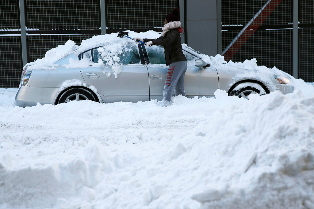 . A woman shovels out her car after a winter storm, Sunday, Jan. 24, 2016, in Philadelphia. (AP Photo/Matt Slocum)