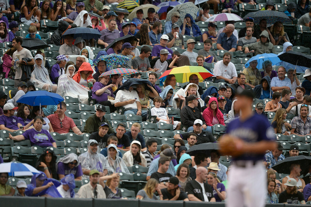 . Colorado Rockies fans bring out the umbrellas as a  rain falls during their game against the San Diego Padres July 7, 2014 at Coors Field. (Photo by John Leyba/The Denver Post)