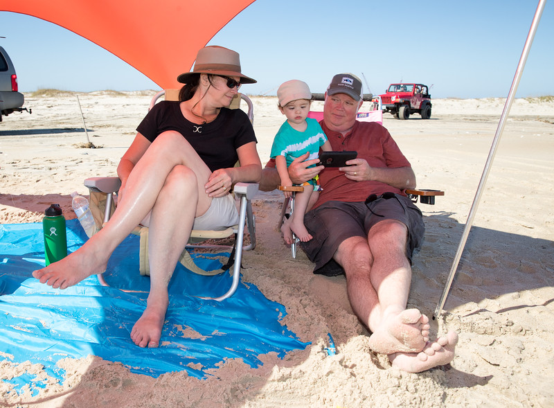 Caleb sitting with mom and dad on the beach.jpg