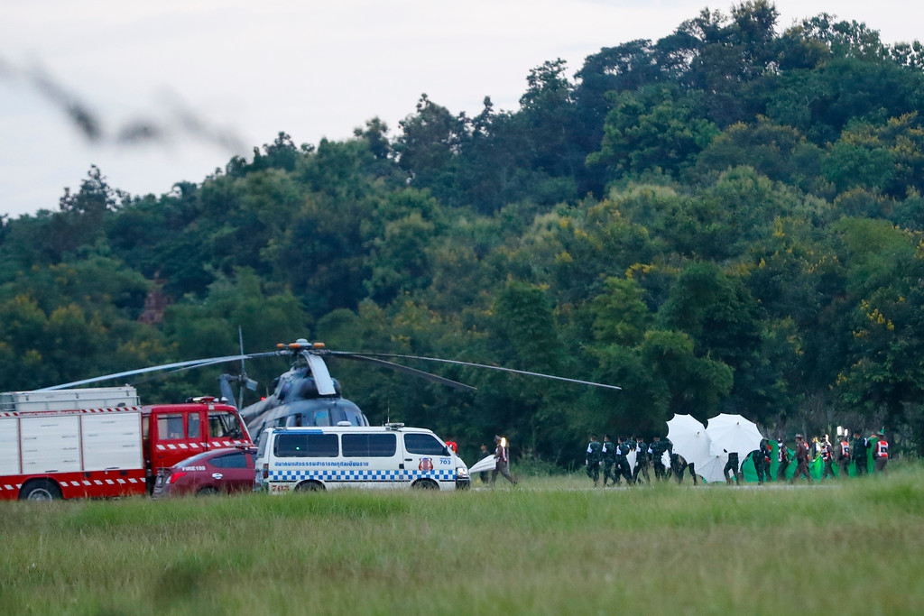 . An emergency team rushes to a helicopter believed to be carrying one of the rescued boys from the flooded cave coming from Mae Sai as divers continue to extract the remaining boys and their coach trapped at Tham Luang cave in the Mae Sai district of Chiang Rai province, northern Thailand, Tuesday, July 10, 2018. Thai Navy SEALs say all 12 boys and their coach were rescued from the cave, ending an ordeal that lasted more than 2 weeks. (AP Photo/Vincent Thian)