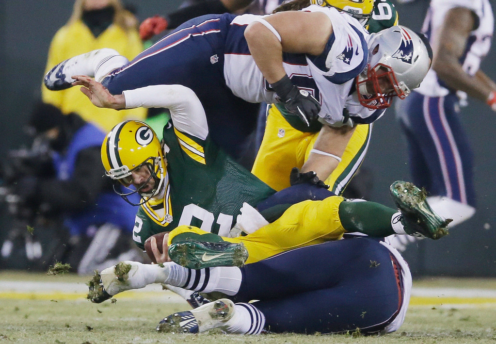 . Green Bay Packers quarterback Aaron Rodgers is sacked by New England Patriots\' Dont\'a Hightower and Zach Moore (90) during the first half of an NFL football game Sunday, Nov. 30, 2014, in Green Bay, Wis. (AP Photo/Tom Lynn)