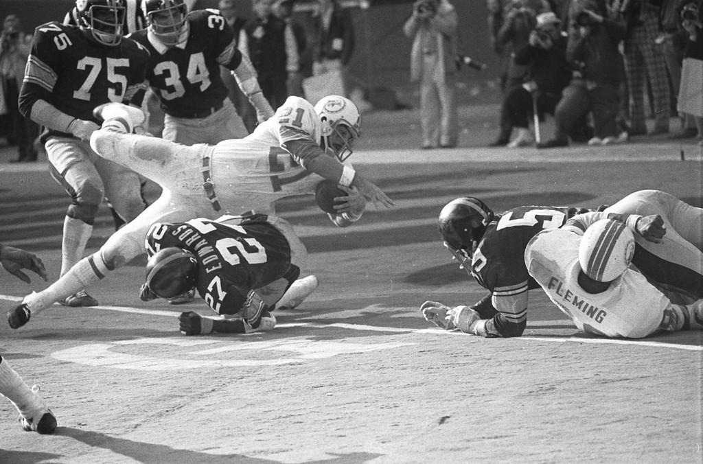 ". Miami Dolphins Jim Kiick goes headfirst over Pittsburgh Steelers"" Glen Edwards Dec. 31, 1972 as Kiick scores in third quarter of the AFC championship game at Pittsburgh\'s Three Rivers Stadium. (AP Photo)"