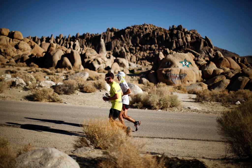 . Carlos Alberto Gomes De Sa of Portugal (R) runs with his pace setter on his way to winning the Badwater Ultramarathon at the foot of Mount Whitney, California July 16, 2013. The 135-mile (217 km) race, which bills itself as the world\'s toughest foot race, goes from Death Valley to Mount Whitney, California in temperatures which can reach 130 degrees Fahrenheit (55 Celsius).  REUTERS/Lucy Nicholson