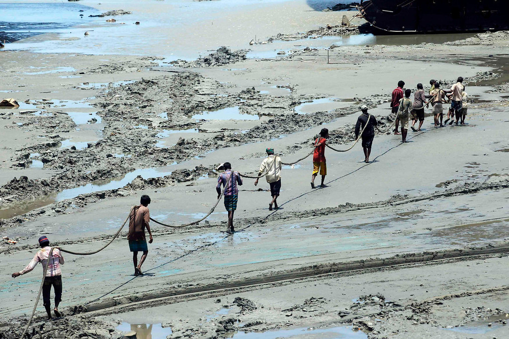 . Workers carry a long rope at a ship-breaking yard in Chittagong, Bangladesh July 16, 2013. Bangladesh is dependent on ship-breaking for its domestic steel requirements. According to a report by the Bangladesh Institute of Labour Studies, around 30,000 workers are employed in the ship-breaking industry in Chittagong, a highly polluted coastal belt of around 20 km (12.4 miles), and environmental organizations have said that the number of accidents and casualties at the yard is believed to be the highest in the region. International attention has been focused on workers\' safety in Bangladesh since the disaster at Rana Plaza, a garment factory complex which collapsed in April, killing 1,132 workers.  REUTERS/Andrew Biraj