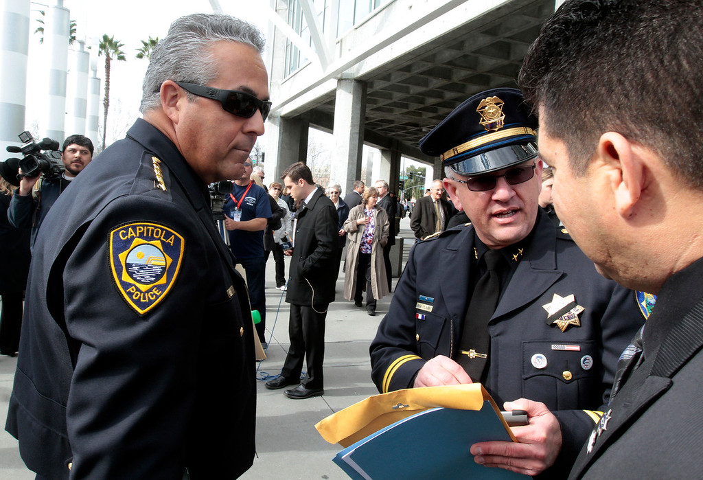 . Capitola Police Chief Rudy Escalante, left, arrives at HP Pavilion Thursday morning as Santa Cruz Police Deputy Chief Steve Clark goes over last minute details of the memorial service for Santa Cruz Police Department\'s fallen officers shortly before the ceremony begins. (Shmuel Thaler/Sentinel)
